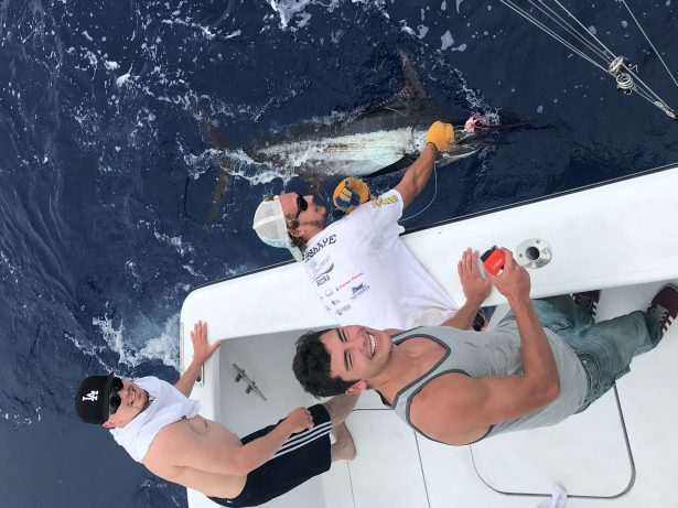 Crew holding a blue marlin beside the boat while fishing in Kona on the Hooked Up.
