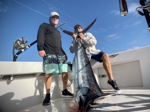 Captain Chuck amd Ryan  holding the bkue Marlin we caught kona fishing