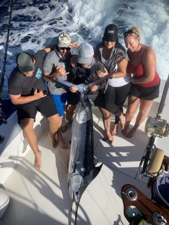 Holding a blur Marlin while kona fishing